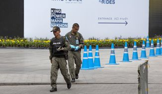 Thai investigators walk in an area that an explosion injured people in Bangkok, Thailand, Friday, Aug. 2, 2019. Thai Prime Minister Prayuth Chan-o-cha on Friday ordered an investigation into several small bombings in Bangkok that took place as Thailand was hosting a high-level meeting attended by U.S. Secretary of State Mike Pompeo and his counterparts from China and several Asia-Pacific countries.(AP Photo/Gemunu Amarasinghe)