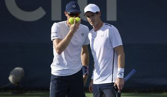 Andy Murray, right, talks with Jamie Murray, left, both of Britain, as they played a doubles match against Raven Klaasen, of South Africa, and Michael Venus, of New Zealand, in the Citi Open tennis tournament, Friday, Aug. 2, 2019, in Washington. (AP Photo/Nick Wass)