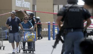 Walmart customers are escorted from the store after a gunman opened fire on shoppers near the Cielo Vista Mall, Saturday, Aug. 3, 2019, in El Paso, Texas. Multiple people were killed and one person was in custody after a shooter went on a rampage at the shopping mall, police in the Texas border town of El Paso said. (Mark Lambie/The El Paso Times via AP) **FILE**