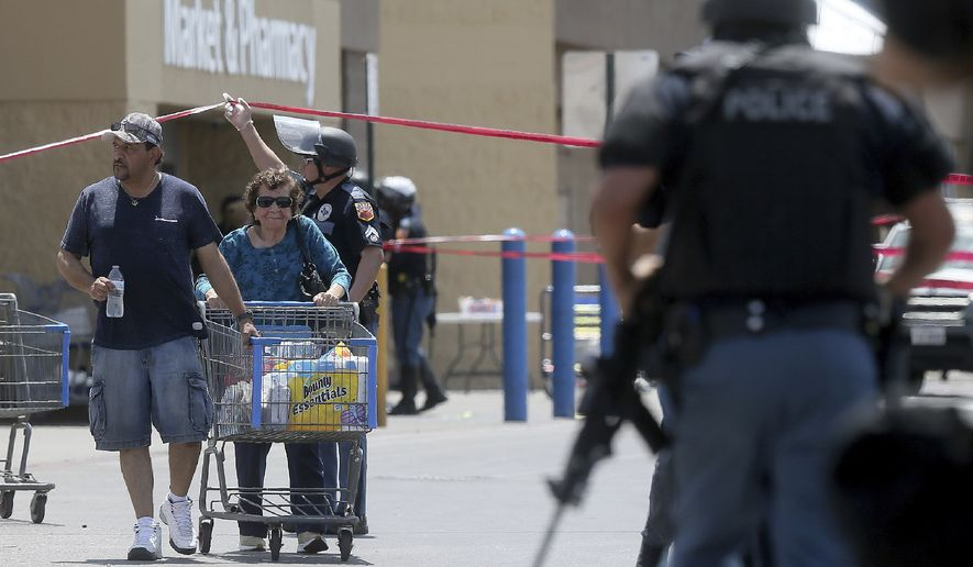 Walmart customers are escorted from the store after a gunman opened fire on shoppers near the Cielo Vista Mall, Saturday, Aug. 3, 2019, in El Paso, Texas. Multiple people were killed and one person was in custody after a shooter went on a rampage at the shopping mall, police in the Texas border town of El Paso said. (Mark Lambie/The El Paso Times via AP)