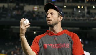 Washington Nationals pitcher Max Scherzer tosses a ball to a fan in the crowd after the ninth inning of a baseball game against the Arizona Diamondbacks Friday, Aug. 2, 2019, in Phoenix. The Nationals defeated the Diamondbacks 3-0. (AP Photo/Ross D. Franklin) ** FILE **