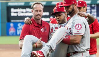 Los Angeles Angels starting pitcher Felix Pena is carried off the field by teammate Albert Pujols and an unidentified trainer during the second inning of a baseball game against the Cleveland Indians in Cleveland, Saturday, Aug. 3, 2019. (AP Photo/Phil Long)