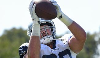 Dallas Cowboys tight end Jason Witten catches the ball from a passing machine at the NFL football team's training camp in Oxnard, Calif., Monday, July 29, 2019. (AP Photo/Michael Owen Baker)