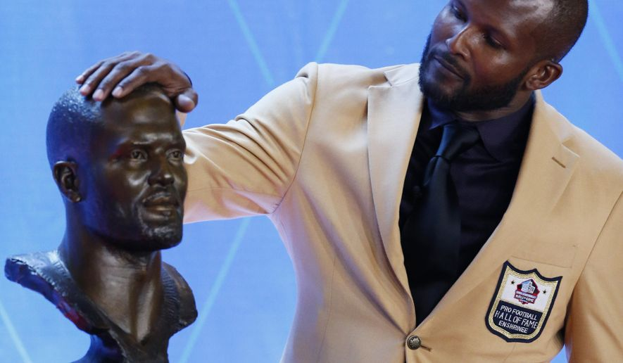 Former NFL player Champ Bailey touches a bust of himself during the induction ceremony at the Pro Football Hall of Fame, Saturday, Aug. 3, 2019, in Canton, Ohio. (AP Photo/Ron Schwane) ** FILE **