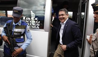 FILE - In this March 11, 2019 file photo, Honduran President Juan Orlando Hernandez steps off a bus at an event to inaugurate a new police force to safeguard urban transit, in Tegucigalpa, Honduras. U.S. federal prosecutors have on Friday, Aug. 2, accused Honduran President Juan Orlando Hernandez of having used $1.5 million in drug trafficking proceeds to secure the presidency.  (AP Photo/Fernando Antonio, File)