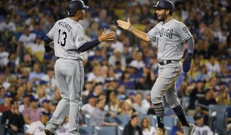 San Diego Padres' Eric Hosmer, right, is congratulated by Manny Machado as he scores on a double by Josh Naylor during the sixth inning of the team's baseball game against the Los Angeles Dodgers on Friday, Aug. 2, 2019, in Los Angeles. (AP Photo/Mark J. Terrill)