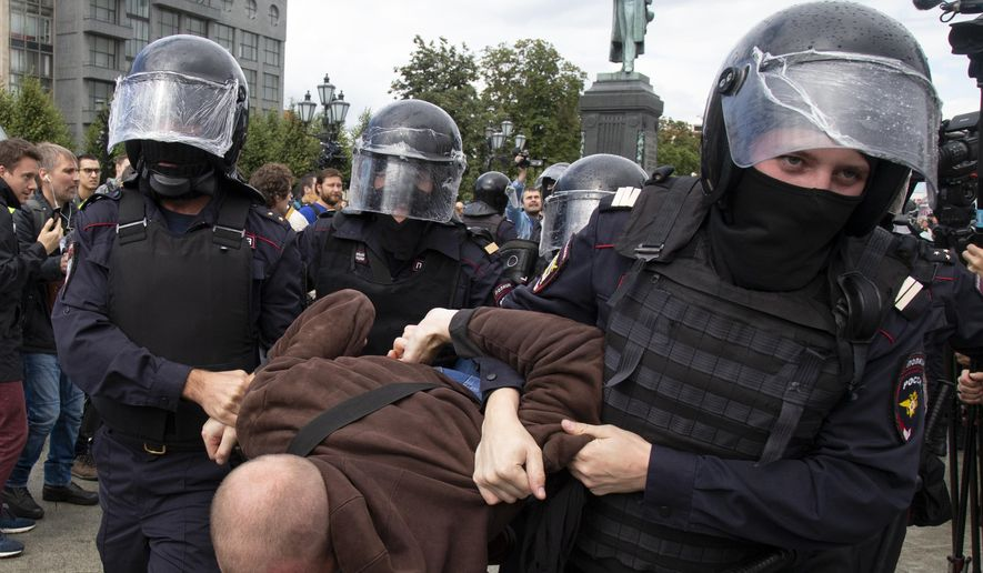 Police officers detain a protestor, during an unsanctioned rally in Pushkin Square in Moscow, Russia, Saturday, Aug. 3, 2019. Moscow police detained more than 300 people Saturday who are protesting the exclusion of some independent and opposition candidates from the city council ballot, a monitoring group said. (AP Photo/Alexander Zemlianichenko)