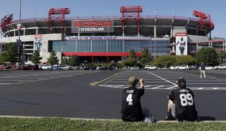 FILE - In this Sept. 10, 2017, file photo, Devin Walsh, left, and his father, Gerard Walsh, wait outside Nissan Stadium before an NFL football game between the Tennessee Titans and the Oakland Raiders  in Nashville, Tenn. The Titans have had trouble filling their stadium for years and have needed the help of visiting fans to sell as many seats as they have. The sales office stays busy pitching ticket deals to a stadium built in the late 1990s. Not even the first three-year stretch of winning seasons since relocating to Tennessee has helped yet. So the Titans are getting more creative. (AP Photo/James Kenney, File)