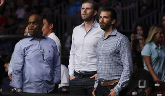 Donald Trump Jr., right, and Eric Trump, center, watch the post fight ceremony of a lightweight mixed martial arts bout between Jim Miller and Clay Guida at UFC Fight Night Saturday, Aug. 3, 2019, in Newark, N.J. Guida stopped Miller in the first round. (AP Photo/Frank Franklin II)