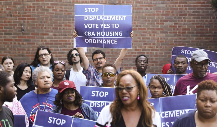 In this Tuesday, July 23, 2019, file photo, activist Jose Reuena, center in back row, holds a placard during a news conference and rally in Chicago. (AP Photo/Amr Alfiky)