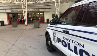 A police cruiser sits outside the Dayton Convention Center, where families of victims were asked to check in Sunday, Aug. 4, 2019, for news about their loved ones in Dayton, Ohio. (AP Photo/Julie Carr Smyth)