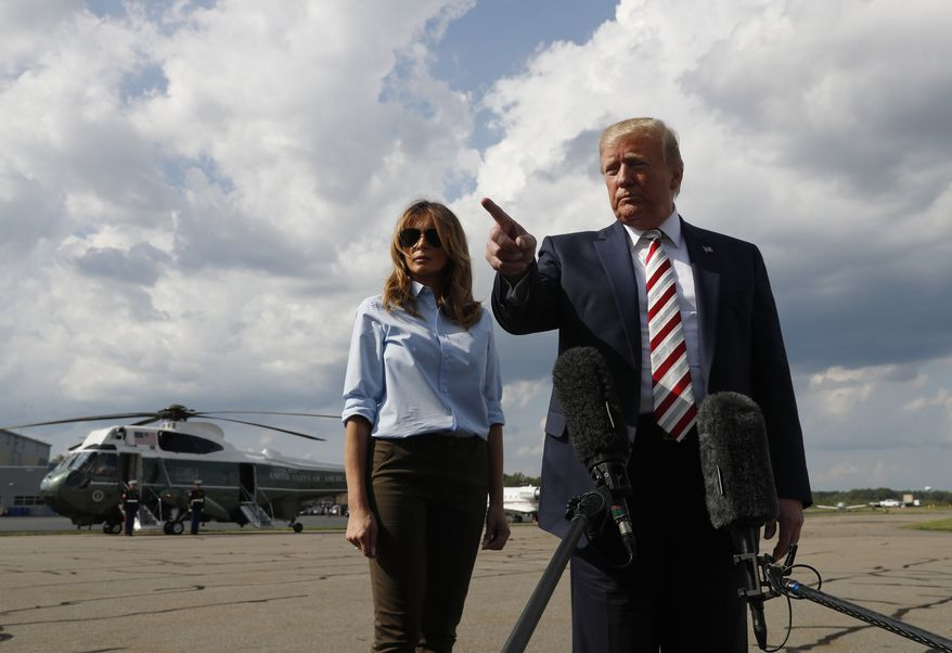 President Donald Trump, with first lady Melania Trump, spoke to the media Sunday before boarding Air Force One about two mass shootings this weekend. (Associated Press)