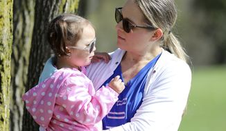 In this April 23, 2019 photo, Lisa Kum is seen in a park near Madison, Wis., with her daughter Emma, 2. In 2014, Kums husband Sothy Kum allowed an acquaintance to pay him to send marijuana to his house. He was convicted of possession of marijuana with the intent to deliver and served a year in prison. He was later detained by Immigration and Customs Enforcement and deported in April 2018. Sothy Kum is a Cambodian refugee who left the country as a child. He is among thousands of immigrants deported each year for marijuana-related charges. (Coburn Dukehart/Wisconsin Watch via AP)