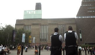 "Emergency crews attending a scene at the Tate Modern art gallery, London, Sunday, Aug. 4, 2019. London police say a teenager was arrested after a child ""fell from height"" at the Tate Modern art gallery. The Metropolitan Police Service said on Twitter that the child was taken to a hospital in an air ambulance, adding ""We await an update on his condition."" (Yui Mok/PA via AP)"