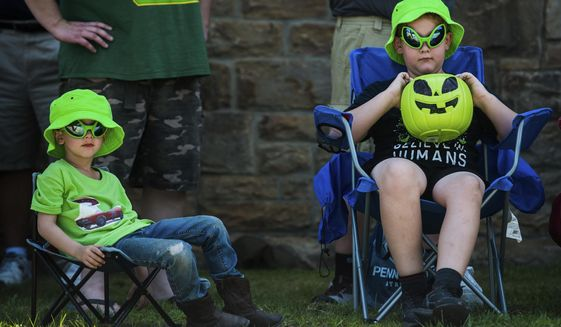 """Robert Goodling, 8, right, watches the parade with his younger brother, Lincoln Goodling, 4, left, on Saturday, July 27, 2019 during the Kecksburg UFO Festival in Kecksburg, Pa.  While the Kecksburg UFO sighting has become a quaint part of local lore, more recent reports of unexplained aerial phenomena are getting serious attention from Congress, the U.S. military and longtime UFO watchers. """"It's not going away,"""" said retired journalist Bob Gatty. Meanwhile, longtime local UFO researcher Stan Gordon reports a """"surge"""" in sightings of unexplained phenomena in western Pennsylvania.  (Shane Dunlap/Pittsburgh Tribune-Review via AP)"""