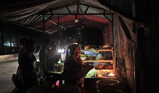 A vendor is illuminated by candle light as she serves customers at her stall during a power outage in Jakarta, Indonesia, Sunday, Aug. 4, 2019. Indonesia's sprawling capital and other parts of Java island have been hit by a massive power outage affecting millions of people. (AP Photo/Dita Alangkara)