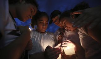 People gather in Juarez, Mexico, Saturday, Aug. 3, 2019, in a vigil for the three Mexican nationals who were killed in an El Paso shopping-complex shooting. Twenty people were killed and more than two dozen injured in a shooting Saturday in a busy shopping area in the Texas border town of El Paso, the state's governor said. (AP Photo/Christian Chavez)