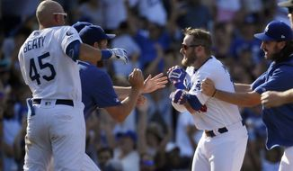 Los Angeles Dodgers' Max Muncy, second from right, is swarmed by teammates after hitting a walkoff double during the ninth inning of a baseball game against the San Diego Padre,s Sunday, Aug. 4, 2019, in Los Angeles. (AP Photo/Mark J. Terrill)