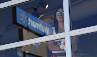 A restaurant employee looks at the scene of a mass shooting at a shopping complex Sunday, Aug. 4, 2019, in El Paso, Texas. (AP Photo/John Locher)