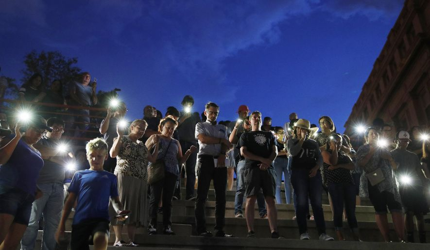 People attend a vigil for victims of the shooting Saturday, Aug. 3, 2019, in El Paso, Texas. A young gunman opened fire in an El Paso, Texas, shopping area during the busy back-to-school season, leaving multiple people dead and more than two dozen injured. (AP Photo/John Locher)