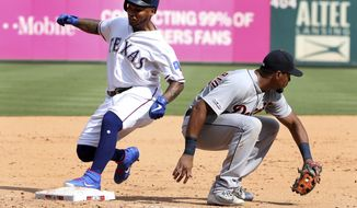 Texas Rangers Willie Calhoun, left, gets to third in front of Detroit Tigers third baseman Jeimer Candelario, right, for a three-run triple during the seventh inning of a baseball game Sunday, Aug 4, 2019, in Arlington, Texas. (AP Photo/Michael Ainsworth)