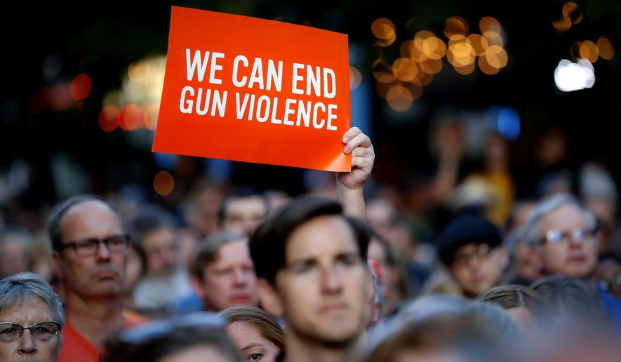Mourners gather for a vigil at the scene of a mass shooting, Sunday, Aug. 4, 2019, in Dayton, Ohio. A masked gunman in body armor opened fire early Sunday in the popular entertainment district in Dayton, killing several people, including his sister, and wounding dozens before he was quickly slain by police, officials said.  (AP Photo/John Minchillo)
