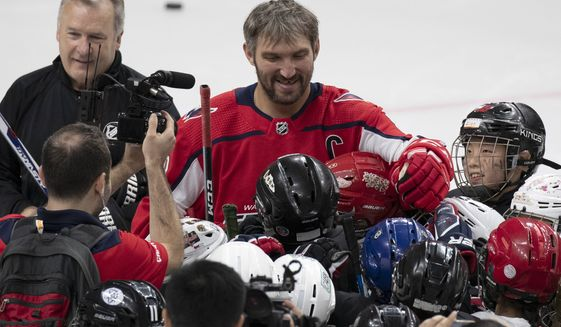 Washington Capitals' Alex Ovechkin reacts as young Chinese ice hockey players surround him at the end of a clinic at the Shougang Sports Complex in Beijing on Monday, Aug. 5, 2019. (AP Photo/Ng Han Guan) ** FILE **