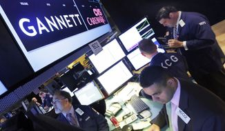 In this Aug. 5, 2014, file photo, specialist Michael Cacace, foreground right, works at the post that handles Gannett on the floor of the New York Stock Exchange. Two of the country's largest newspaper companies announced Monday, Aug. 5, 2019, that have agreed to combine in the latest media deal driven by the industry's struggles with a decline of printed editions. GateHouse Media, a chain backed by an investment firm, is buying USA Today owner Gannett Co. (AP Photo/Richard Drew, File) **FILE**