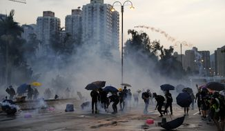 Protesters throw back tear gas canisters in Hong Kong on Monday, Aug. 5, 2019. Droves of protesters filled public parks and squares in several Hong Kong districts on Monday in a general strike staged on a weekday to draw more attention to their demands that the semi-autonomous Chinese city's leader resign. (AP Photo/Kin Cheung)