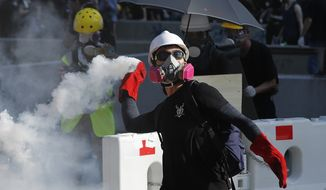 A protester throws back a tear gas canister in Hong Kong on Monday, Aug. 5, 2019. Droves of protesters filled public parks and squares in several Hong Kong districts on Monday in a general strike staged on a weekday to draw more attention to their demands that the semi-autonomous Chinese city's leader resign.(AP Photo/Vincent Thian)