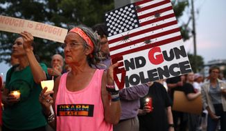 Sandi Lisko attends a vigil for recent victims of gun violence outside the National Rifle Association's headquarters building, Monday, Aug. 5, 2019, in Fairfax, Va. (AP Photo/Patrick Semansky)
