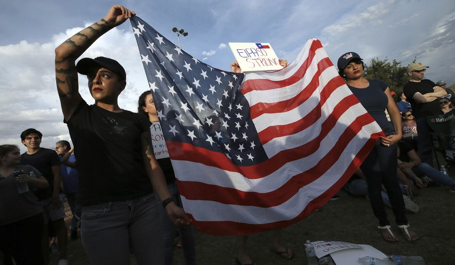 Twin sisters Jessica Torres, left, and Danielle Novoa hold an American flag during the Hope Border Institute prayer vigil for the victims of Saturday's mass shooting at a shopping complex,  Sunday, Aug. 4, 2019 in El Paso, Texas. (Mark Lambie/The El Paso Times via AP)