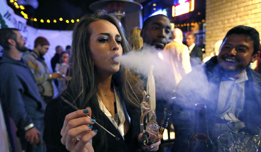 In this Dec. 31, 2013 file photo, a woman smokes marijuana during a Prohibition-era themed New Year's Eve party at a bar in Denver, the day before Colorado allowed retail sales of marijuana to those 21 and over.  (AP Photo/Brennan Linsley,File)  **FILE**