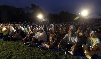 FILE - In this Aug. 5, 2013, file photo hundreds participate in a candlelight vigil at the Sikh Temple of Wisconsin to mark the one-year anniversary of the shooting rampage that left six dead in Oak Creek, Wis. The white supremacist gunman, who wounded five other worshippers and an Oak Creek police officer, killed himself in the parking lot. (AP Photo/Morry Gash, File)