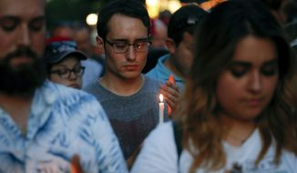 Mourners bow their heads in prayer as they gather for a vigil at the scene of a mass shooting, Sunday, Aug. 4, 2019, in Dayton, Ohio. Multiple people in Ohio were killed in the second mass shooting in the U.S. in less than 24 hours. (AP Photo/John Minchillo)