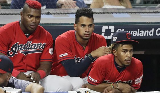 From left to right, Cleveland Indians' Yasiel Puig, Oscar Mercado and Francisco Lindor watch the ninth inning in a baseball game against the Texas Rangers, Monday, Aug. 5, 2019, in Cleveland. (AP Photo/Tony Dejak)