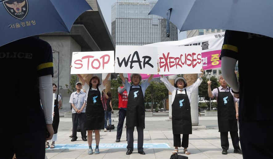 Protesters hold up placards to oppose planned joint military exercises between South Korea and the United States near the U.S. Embassy in Seoul, South Korea, Monday, Aug. 5, 2019. Both countries are preparing to hold their annual joint military exercises despite warnings from North Korea that the drills could derail the fragile nuclear diplomacy, Seoul's military said Friday. (AP Photo/Ahn Young-joon)