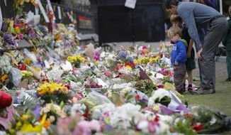 FILE - In this March 18, 2019, file photo, mourners lay flowers on a wall at the Botanical Gardens in Christchurch, New Zealand. The El Paso massacre is the latest attack in which the gunman appears to have praised the March shootings in Christchurch, where an Australian white supremacist is charged with killing 51 worshippers at two mosques. (AP Photo/Vincent Thian, File)