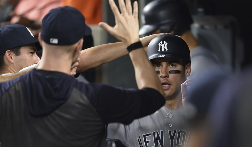 New York Yankees' Mike Tauchman is congratulated after scoring against the Baltimore Orioles in the fifth inning of a baseball game, Monday, Aug. 5, 2019, in Baltimore. (AP Photo/Gail Burton)
