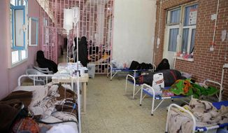 In this March 30, 2019, file photo, women are treated for suspected cholera infection at Al-Sabeen hospital, in Sanaa, Yemen. An Associated Press investigation found some of the United Nations aid workers sent in to Yemen amid a humanitarian crisis caused by five years of civil war have been accused of enriching themselves from an outpouring of donated food, medicine and money. (AP Photo/Hani Mohammed, File)
