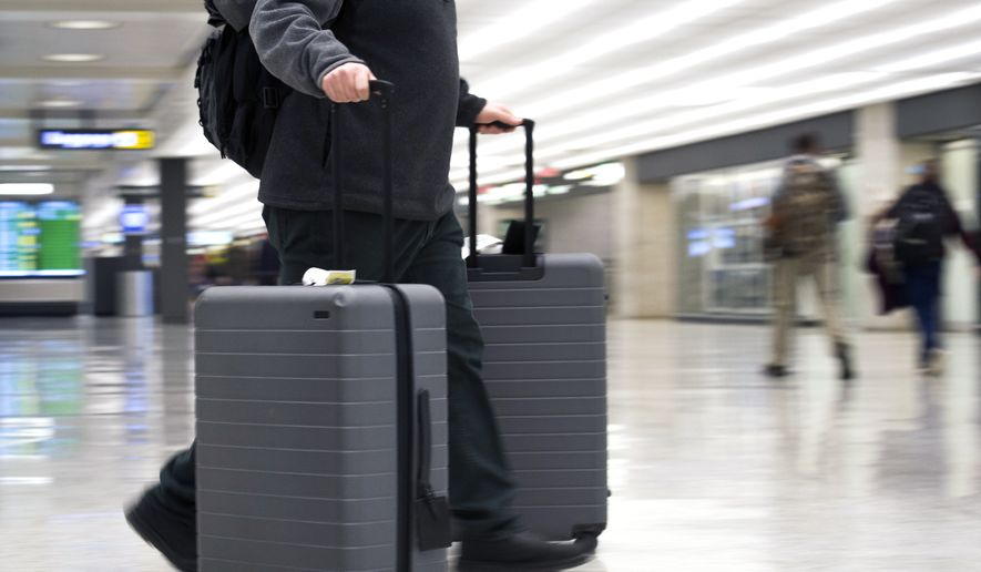 In this March 26, 2019, file photo, an airline passenger walk in the arrivals terminal at Dulles International Airport in Dulles, Va. Newly documents filed in a federal lawsuit claim that U.S. government searches of phones and laptops at airports are on the rise and are being conducted for reasons beyond immigration and customs enforcement. There were 33,295 searches in fiscal 2018.  (AP Photo/Cliff Owen, File)