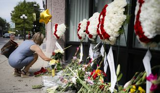 Mourners bring flowers to a makeshift memorial for the slain in the Oregon District after a mass shooting that occurred early Sunday morning, Tuesday, Aug. 6, 2019, in Dayton. (AP Photo/John Minchillo)