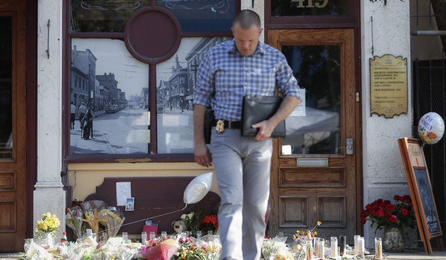 A Dayton Police officer performs a grid search beside a makeshift memorial for the slain and injured in the Oregon District after a mass shooting that occurred early Sunday morning, Tuesday, Aug. 6, 2019, in Dayton.  Facing pressure to take action after the latest mass shooting in the U.S., Ohio's Republican governor urged the GOP-led state Legislature Tuesday to pass laws requiring background checks for nearly all gun sales and allowing courts to restrict firearms access for people perceived as threats.  (AP Photo/John Minchillo)