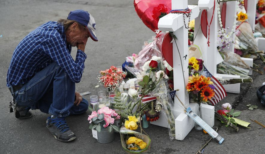 A man cries beside a cross at a makeshift memorial near the scene of a mass shooting at a shopping complex Tuesday, Aug. 6, 2019, in El Paso, Texas.  The border city jolted by a weekend massacre at a Walmart absorbed more grief Monday as the death toll climbed and prepared for a visit from President Donald Trump over anger from El Paso residents and local Democratic leaders who say he isn't welcome and should stay away. (AP Photo/John Locher) **FILE**
