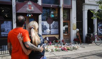 Mourners pause at a makeshift memorial for the slain and injured outside Ned Peppers bar in the Oregon District after a mass shooting that occurred early Sunday morning, Tuesday, Aug. 6, 2019, in Dayton. (AP Photo/John Minchillo)