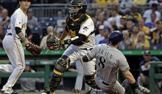 Milwaukee Brewers' Ryan Braun (8) scores on a double by Yasmani Grandal off Pittsburgh Pirates starting pitcher Steven Brault, left rear, as catcher Elias Diaz waits for the late relay throw during the fifth inning of a baseball game in Pittsburgh, Tuesday, Aug. 6, 2019. (AP Photo/Gene J. Puskar)