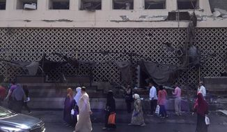 People survey the aftermath of a fiery car crash outside the National Cancer Institute in Cairo, Egypt, Monday, Aug. 5, 2019. The multiple-car crash set off an explosion that ignited a fire at Egypt's main cancer hospital, the government said.(AP Photo/Maya Alleruzzo)