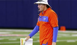 Florida head coach Dan Mullen walks during an NCAA college football practice in Gainesville, Fla., Friday, July 26, 2019. (Brad McClenny/The Gainesville Sun via AP)