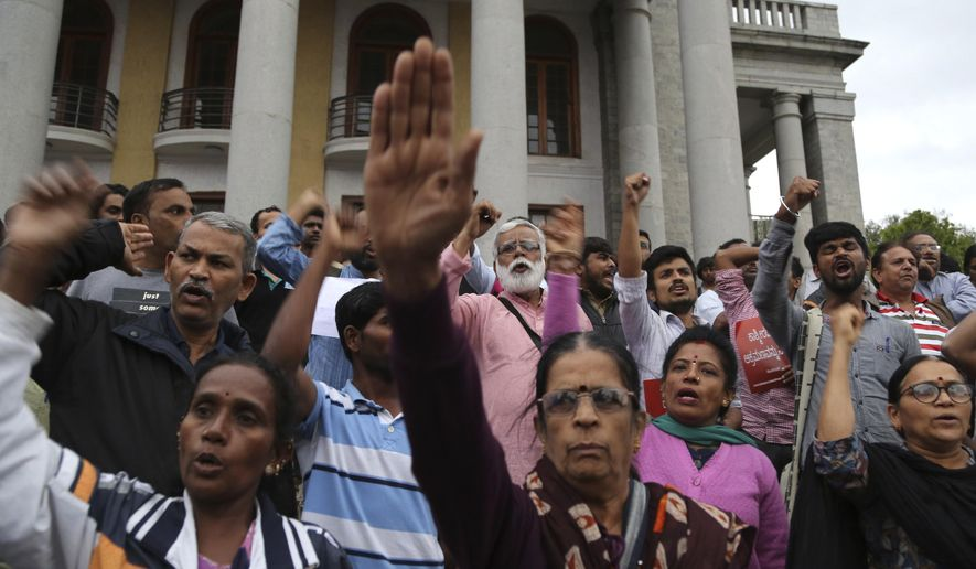Indian activists and others shout slogans during a protest against Indian government revoking Kashmir's special constitutional status in Bangalore, India, Monday, Aug. 5, 2019. India's government has revoked disputed Kashmir's special status with a presidential order as thousands of newly deployed troops arrived and internet and phone services were cut in the restive Himalayan region where most people oppose Indian rule. (AP Photo/Aijaz Rahi)
