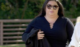 FILE - In this July 16, 2019 file photo, Lee Elbaz arrives at federal court for jury selection in her trial in Greenbelt, Md.  U.S. District Judge George Hazel on Tuesday, Aug. 6, 2019 dismissed one of 12 jurors who have been deliberating for days in the case against Elbaz, an Israeli woman charged with orchestrating a scheme to defraud tens of thousands of investors out of tens of millions of dollars.(AP Photo/Jose Luis Magana, File)